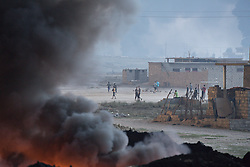 Licensed to London News Pictures. 20/10/2016. Iraqi youths play football between billowing smoke rising from burning oil wells, that have been on fire for around two months, in a residential area in the town of Qayyarah, Iraq. The oil wells, located in a neighbourhood on the edge of the town, were set alight in July by retreating Islamic State militants as part of a scorched earth policy.<br /> <br /> Since being retaken from the Islamic State the town of Qayyarah has become an important staging post for the Iraqi Army, and some US support elements, in the buildup to the Mosul offensive. Photo credit: Matt Cetti-Roberts/LNP