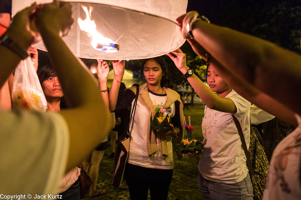 "17 NOVEMBER 2013 - BANGKOK, THAILAND: Students pray before launching  a Yi Peng lantern on Loy Krathong near Wat Yannawa in Bangkok. The Yi Peng lanterns are Loy Krathong tradition in Chiang Mai but they are becoming more popular  in Bangkok and central Thailand. Loy Krathong (also written as Loi Krathong) is celebrated annually throughout Thailand and certain parts of Laos and Burma (in Shan State). The name could be translated ""Floating Crown"" or ""Floating Decoration"" and comes from the tradition of making buoyant decorations which are then floated on a river. Loi Krathong takes place on the evening of the full moon of the 12th month in the traditional and they do this all evening on the 12th month Thai lunar calendar. In the western calendar this usually falls in November. The candle venerates the Buddha with light, while the krathong's floating symbolizes letting go of all one's hatred, anger, and defilements       PHOTO BY JACK KURTZ"