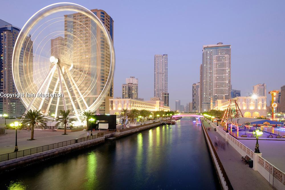 Evening view of Eye of the Emirates ferris wheel and Al Qasba entertainment district in Sharjah United Arab Emirates