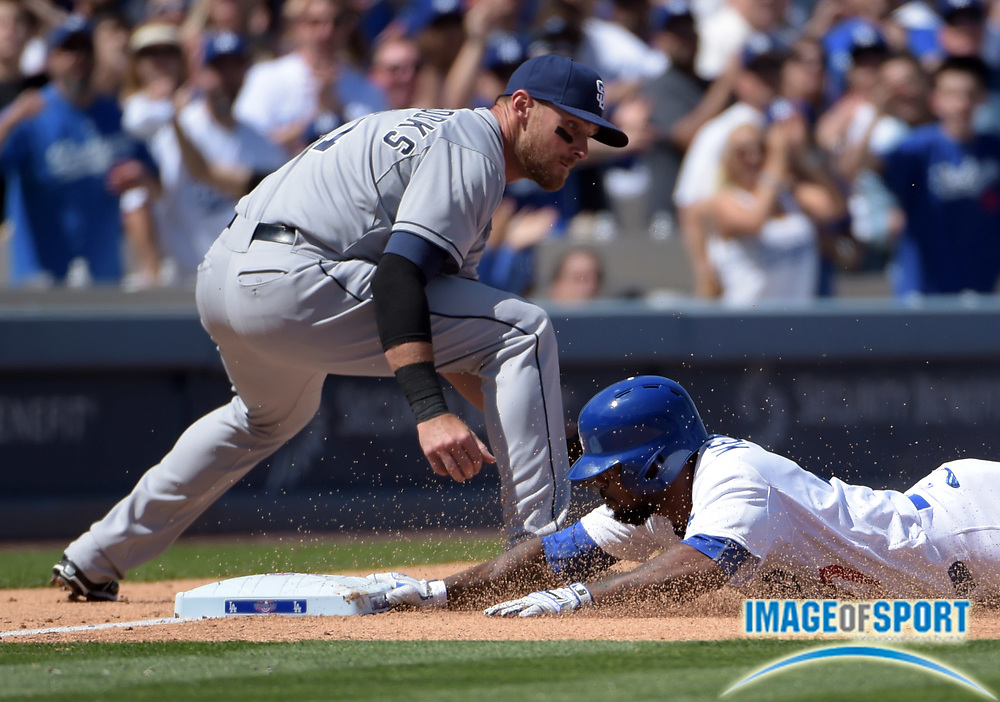 Apr 6, 2015; Los Angeles, CA, USA; Los Angeles Dodgers second baseman Howie Kendrick (47) slides into third base to beat a throw to San Diego Padres third baseman Will Middlebrooks (11) for a triple in the fourth inning in the 2015 MLB opening day game at Dodger Stadium. The Dodgers defeated the Padres 6-3.