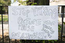 © Licensed to London News Pictures. 18/06/2017. London, UK. A hand written sign asks people to stop taking pictures and selfies at the site of the burnt out Grenfell tower block . The blaze engulfed the 27-storey building killing dozens - with 34 people still in hospital, many of whom are in critical condition. The fire brigade say that they don't expect to find anyone else alive. Photo credit: Peter Macdiarmid/LNP
