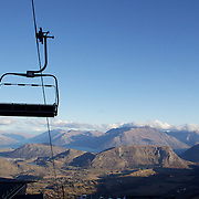 The chair lift at Coronet Peak Ski Field lies dormant with little snow on the hillsides of the Wakatipu Basin in the background showing the extent of the unusually warm weather delaying the start of the ski season in Queenstown, New Zealand..New Zealand sweltered through it's hottest May since record-keeping began with figures issued by climate agency Niwa showed that May was 2.3C warmer than usual. The average monthly temperature was 13.1C, a temperature normally expected for April. The previous hottest May, recorded in 2007, had a mean temperature of 12.4C. Coronet Peak, Queenstown,  South Island, New Zealand, 27th June 2011