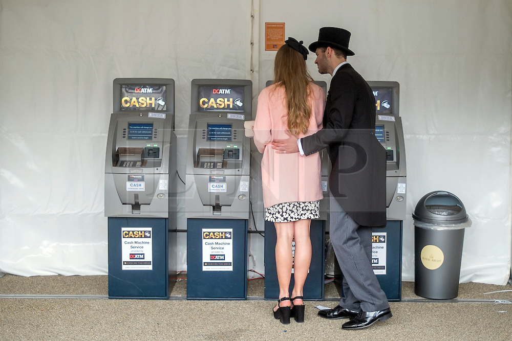 © Licensed to London News Pictures. 18/06/2014. Ascot, UK. A couple get money from an ATM.  Day two at Royal Ascot 18th June 2014. Royal Ascot has established itself as a national institution and the centrepiece of the British social calendar as well as being a stage for the best racehorses in the world. Photo credit : Stephen Simpson/LNP