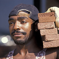 A construction worker in Alexandria, Virginia carries bricks at his job site.