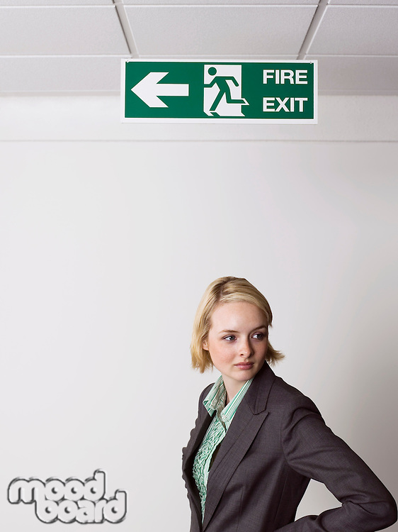 Businesswoman standing under exit sign