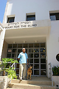 Library for the Blind. A blind man and guide dog at the entrance the library