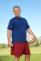 Senior man holding soccer ball in park, portrait