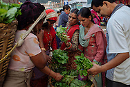 Devaki Aryal (center, with red scarf) sells produce along a busy street in Kathmandu, Nepal. Women carry bundles of produce on their backs to sell in the early morning. If they are caught by police for illegal selling they are fined 1500 Nepalese rupees, or about $15. Aryal says she makes about $9 a day.