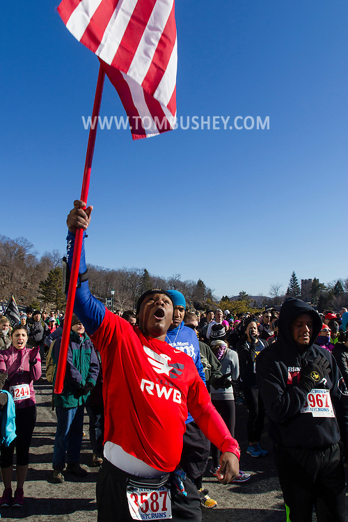 West Point, New York - A runner with team Red, White and Blue holds up an American flag before the3 start of the West Point Half-Marathon Fallen Comrades Run at the United States Military Academy on March 29, 2015.