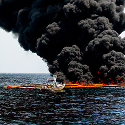 A observation boat is seen in thick oil is seen on the surface as oil boomed off oil is burned on the surface during a controlled burn near the source of the BP Plc Deep Water Horizon oil spill site in the Gulf of Mexico off the coast of Louisiana, U.S., on Thursday, July 15, 2010. Photographer: Derick E. Hingle/Bloomberg