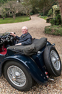 Michael Turner, painter photographed at home with his Jaguar SS100.