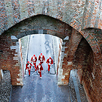 NOALE, ITALY - DECEMBER 18:  A small group of participants  dressed as Father Christmas are seen from above as they walk to take part in the Noale Santa Run on December 18, 2011 in Noale, Italy. Close to two thousand people participated in the third annual Noale Santa Run, one of the largest non competitive Santa Run in Italy.