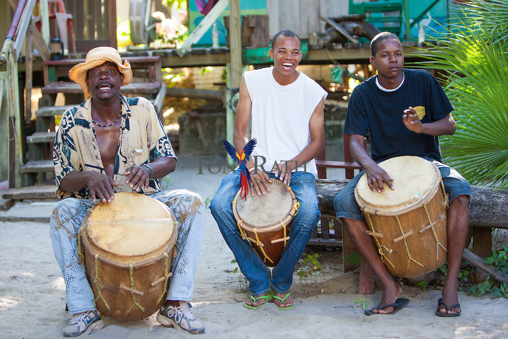 Jabbar Lambey (left), owner and founder of the Lebeha Drumming Center drums with two students in the courtyard of the center, Hopkins Village, Belize.