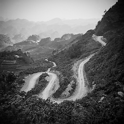 A long winding road cuts through the vast mountainous landscape of Ha Giang Province in Northern Vietnam, Southeast Asia