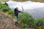 WA11805-00...WASHINGTON - Bow hunter Phil Russell hunting for bull frogs in a small pond.  (MR# R8)