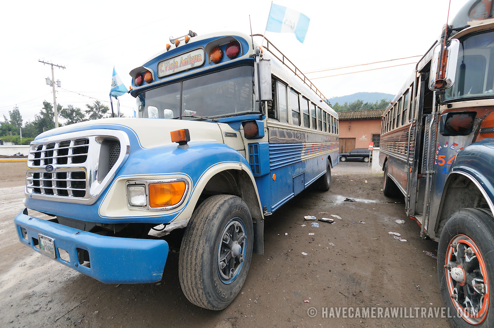A blue and white chicken bus, painted for the Guatemalan national colors, behind the Mercado Municipal (town market) in Antigua, Guatemala. From this extensive central bus interchange the routes radiate out across Guatemala. Often brightly painted, the chicken buses are retrofitted American school buses and provide a cheap mode of transport throughout the country.