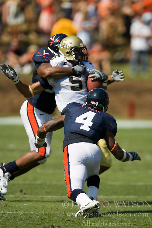 Virginia linebacker Jermaine Dias (57) and cornerback Vic Hall (4) tackle Georgia Tech wide receiver Greg Smith (5).  The Virginia Cavaliers football team faced the Georgia Tech Yellow Jackets at Scott Stadium in Charlottesville, VA on September 22, 2007.