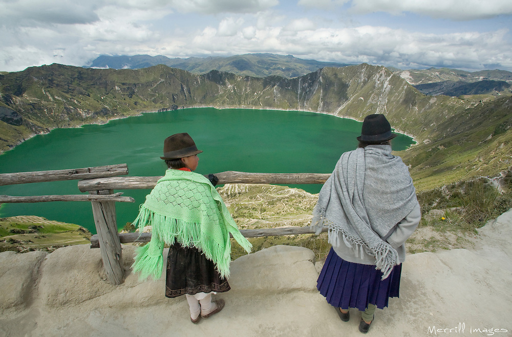 South America, Ecuador, Quilotoa, two women in traditional clothing at Lake Quilotoa, a volcanic crater filled by an emerald lake