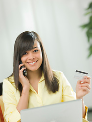 Young woman using credit card over the phone, portrait (Credit Image: © Image Source/ZUMAPRESS.com)