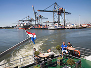 Tourists on a Spido tour boat in container port with quayside cranes and shipping activity, Port of Rotterdam, Netherlands