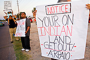 03 APRIL 2008 -- GUADALUPE, AZ:  People line the streets in Guadalupe, AZ, protesting against Maricopa County Sheriff Joe Arpaio's high profile zero tolerance anti crime sweep in Guadalupe Thursday. The Maricopa County Sheriff's Department has started high profile zero tolerance crime sweeps targeting illegal immigrants but also arresting anyone they find breaking the law or with outstanding warrants. All of the previous sweeps have been in Phoenix city limits. This was the first one outside Phoenix, Guadalupe is a working class unincorporated town south of Phoenix. Most of the town's residents are Native Americans and Hispanics and hundreds of people lined the street to protest the sweep.  In 2011, the US Department of Justice issued a report highly critical of the Maricopa County Sheriff's Department and the jails. The DOJ said the Sheriff's Dept. engages in widespread discrimination against Latinos during traffic stops and immigration enforcement, violates the rights of Spanish speaking prisoners in the jails and retaliates against the Sheriff's political opponents.     PHOTO BY JACK KURTZ