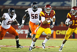 September 11, 2010; Los Angeles, CA, USA;  Southern California Trojans running back Dillon Baxter (28) rushes past Virginia Cavaliers linebacker Aaron Taliaferro (52) and defensive end Cam Johnson (56) during the second quarter at the Los Angeles Memorial Coliseum. USC defeated Virginia 17-14.