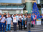 """20 DECEMBER 2013 - BANGKOK, THAILAND: Office workers stand on the sidewalk and watch an anti-government protest on Silom Road. Many of the protestors are members of the Thai middle class, and workers in the offices and banks along Silom Road. Thousands of anti-government protestors, supporters of the so called Peoples Democratic Reform Committee (PRDC), jammed the Silom area, the """"Wall Street"""" of Bangkok, Friday as a part of the ongoing protests against the caretaker government of Yingluck Shinawatra. Yingluck dissolved the Thai Parliament earlier this month and called for national elections on Feb. 2, 2014. The protestors want the elections postponed and the caretaker government to step down. The Thai election commission ruled Friday that the election would go on dispite the protests.          PHOTO BY JACK KURTZ"""