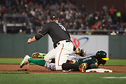 San Francisco Giants first baseman Brandon Belt (9) attempts to pick off Oakland Athletics center fielder Rajai Davis (11) at first base at AT&T Park in San Francisco, California, on March 30, 2017. (Stan Olszewski/Special to S.F. Examiner)