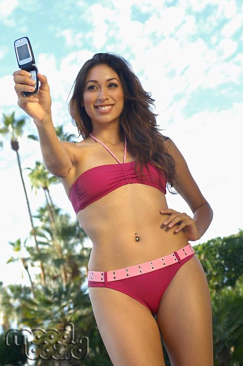 Woman in bikini taking self portrait with mobile phone