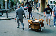 A suited street vender sells bread from a rolling basket in Athens, Greece, Europe.