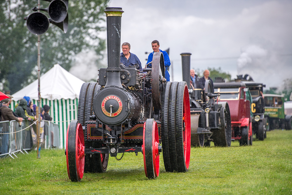 Two mature males drive a vintage steam engine tractor in parade, Masham, North Yorkshire, UK