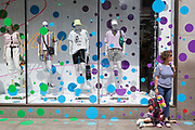 A woman and child wait outside the spotted-theme window display of Topshop on Oxford Street, on 2nd July 2019, in London, England.