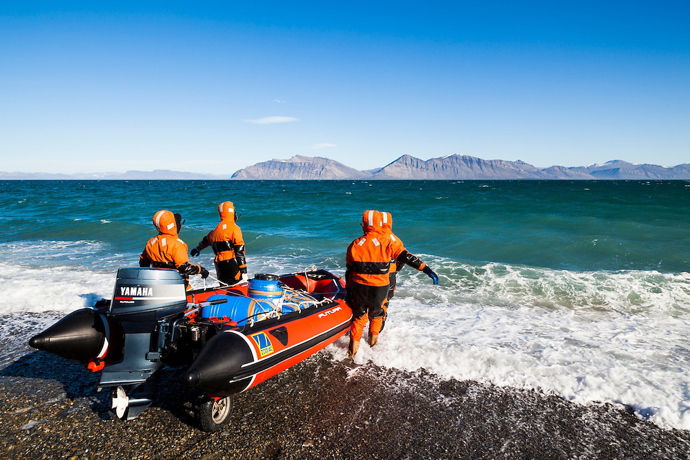 Researchers, dressed in survival suits, launch an inflatable boat into the water to transport heavy equipment up the coast at the Polish field station in Calypsobyen, Svalbard.