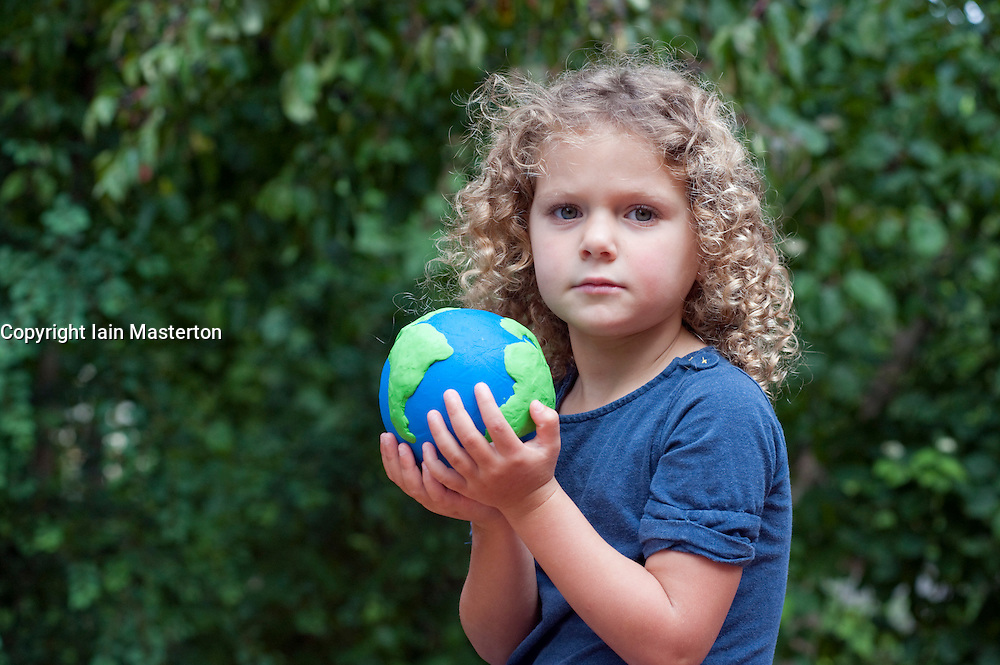 young girl holding a model of planet Earth