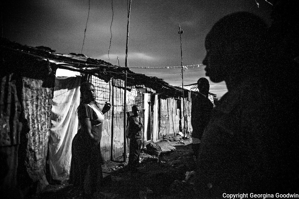 Night closes in on the bottom end of Kawangware Street, the area where many rape incidences have occurred. Since the installation of the flood light further down in December 2012, a joint initiative of the Kenya Government and Safaricom who pay the electricity fee, the incidences of rape have been reduced. <br /> This image is from a series focusing on and around the rape and the women victims that occur every half a day in Mugumoini Village in Nairobi's Southlands, a slum home to 20,000 people in abject poverty with little or no income, with the aim of creating exposure and empowerment for change. &copy;GGoodwin