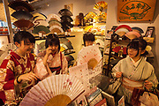 Japanese women in traditional kimono dresses shopping for fans and jewellery, Kyoto, Japan