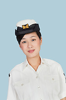 Portrait of a beautiful young US Navy officer over light blue background