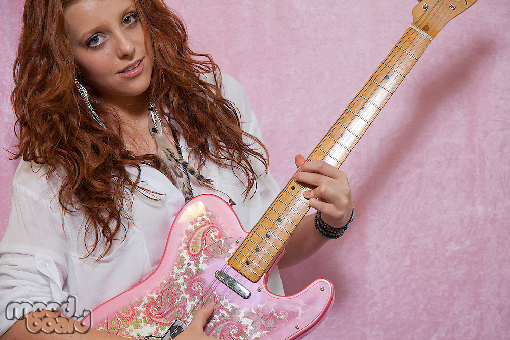 Pretty teenage girl playing guitar