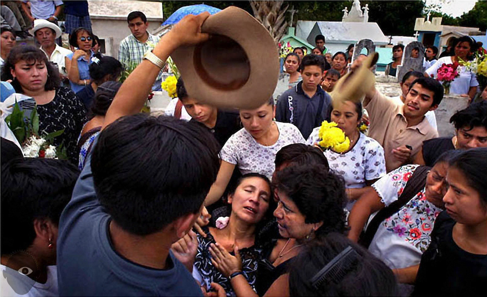 At the cemetery in Mani,Yucatan,  family members and friends work to revive Jose Mejia's widow, Paula Villacis Lopez, who fainted as her husband's casket was lowered in the ground.