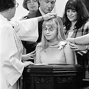 Jessica Black, 13, center, is surrounded by her family and friends as Presbyterian Pastor Ellen McGormley of Monroe, Mich. baptizes and confirms the girl in one ceremony. Black, who had not been baptized as a child, had just completed a 13-week long confirmation course. 1999 Photo by Roger S. Duncan.