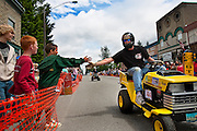 "Marc Kroetch, right, gives a drive-by high five to Stephen Loftis, left, on Kroetch's racing lawnmower ""Mow Heat Oh!"" during the Big Back-In on Maine Street in Spirit Lake. Kroetch along with several others began the annual Father's Day tradition of the Big Back-In in Spirit Lake ten years ago as a way to fundraise for city projects.."