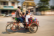 02 MARCH 2014 - MYAWADDY, KAYIN, MYANMAR (BURMA): A pedicab driver takes a family into Myawaddy, Myanmar. Pedicabs are still used in much of Myanmar (Burma). Myawaddy is separated from the Thai border town of Mae Sot by the Moei River. Myawaddy is the most important trading point between Myanmar and Thailand.   PHOTO BY JACK KURTZ