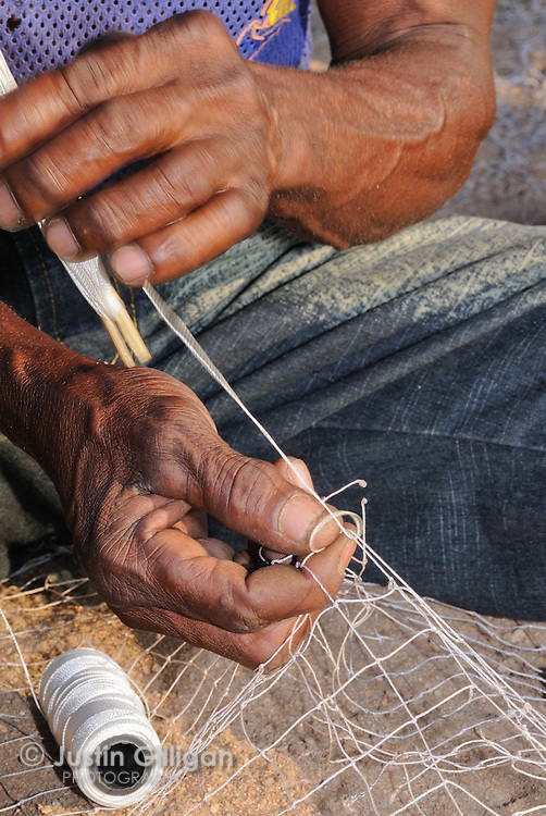 Richard Pofera repairs fishing net at Cape Maclear, Lake Malawi, Malawi.
