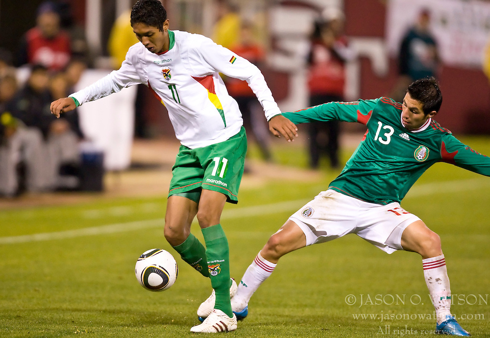 February 24, 2010; San Francisco, CA, USA;  Bolivia midfielder Samuel Galindo (11) is defended by Mexico midfielder Luis Miguel Noriega (13) during the second half at Candlestick Park. Mexico defeated Bolivia 5-0.