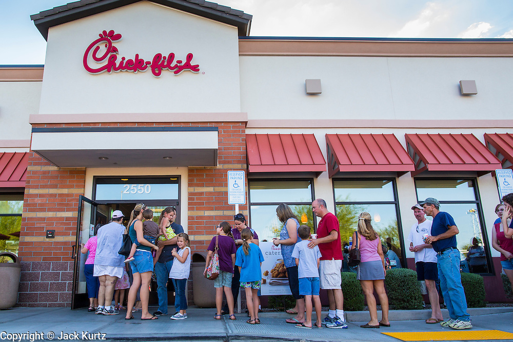 01 AUGUST 2012 - CHANDLER, AZ:  People wait to get into a Chick-fil-A in for dinner Wednesday. Thousands of people stood in line for up to an hour at the Chick-fil-A in Chandler, AZ, a suburb of Phoenix Wednesday after MIKE HUCKABEE, the former governor of Arkansas and Fox News host, called for a national ''Chick-fil-A Appreciation Day,'' a day on which he encouraged people to patronize the fast food chain, this after DAN CATHY, President and CEO of Chick-fil-A, who is a fundamentalist Christian, made public his views against same sex marriage, causing an outcry from political leaders and Gay rights advocates.   PHOTO BY JACK KURTZ