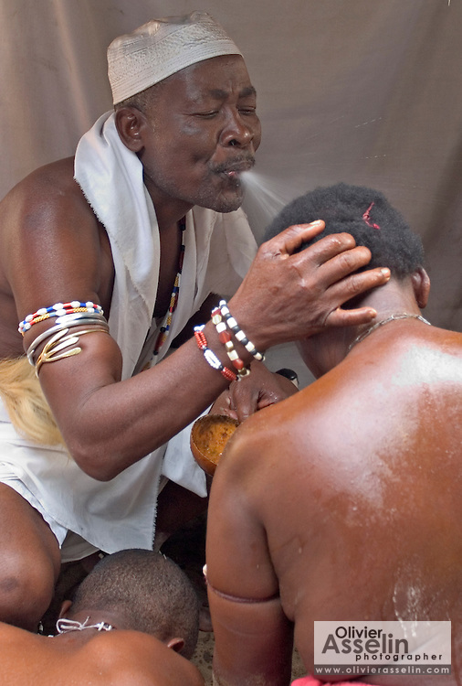 "Head priest spitting gin on shrine servant to purify her during a ""coming out"" ceremony at a fetish shrine in Aflao, Volta Region, Eastern Ghana. A woman was released after spending three months in a small, dark room, hoping that she'd then be able to find a husband. Despite most Ghanaians being adamant followers of christianism or islam, many of them still maintain traditional beliefs. When facing a problem of any nature, some people will visit a local fetish shrine, looking for help. The main priest will consult the oracles and tell the person in need what has to be done for the problem to go away. People will typically be asked to ""serve"" the shrine for weeks, sometimes months, as their families pay the priest for their upkeep."