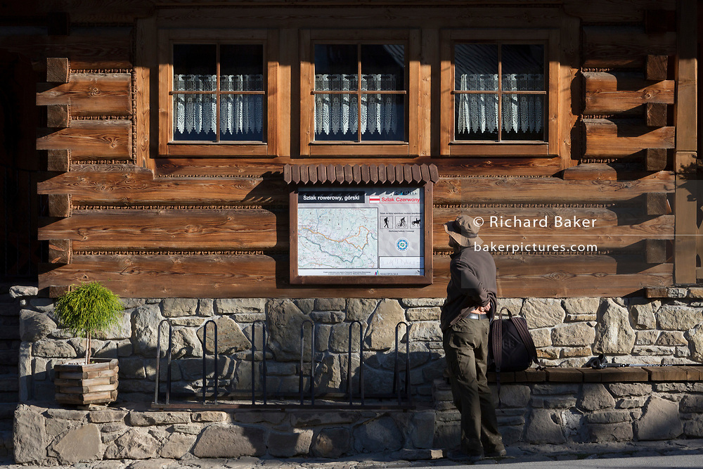 A walker and hiking trail map outside the Bocowka log restaurant, a traditional mountain log cabin in southern Poland, on 21st September 2019, in Jaworki, near Szczawnica, Malopolska, Poland.