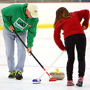 Bill Clawson, left and Abagail Barman sweep a stone during a curling match at the Wilmington Ice House. (Jason A. Frizzelle)