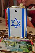 Donating money in a Jewish National Fund (Keren Kayemet LeYisrael JNF or KKL) collection box