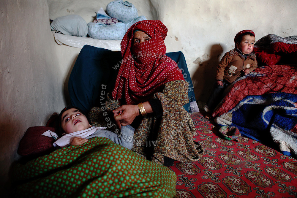 Nazifah, a 48-year-old widow, is holding Wahidullah's hand, her 5-year-old disabled grandson while Najibullah, 3, (Right) is standing in the back, inside the cave where they now live since six years in Bamyan, central Afghanistan, an area mostly populated by Hazaras. A historically persecuted minority (15%) due to more lenient Islamic faith and characteristic 'Eastern' lineaments, Hazaras constitute the 70% of Bamyan's population.
